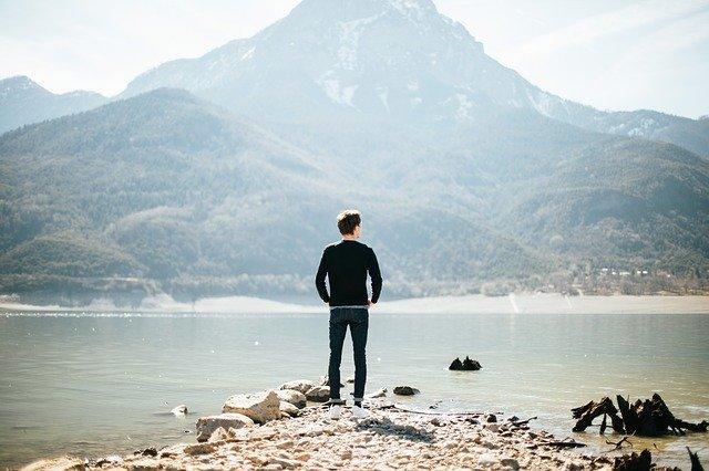 man looking at lake